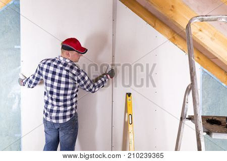 Construction worker holding gypsum board. Attic renovation. Installation of drywall