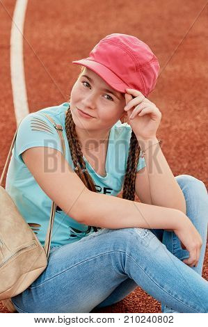 A young bright girl loves sports.sporty girl in the baseball cap pink.Closeup portrait of a teenage girl.