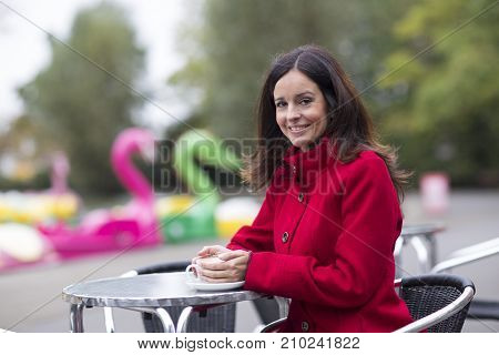 young woman enjoying a coffee in the park