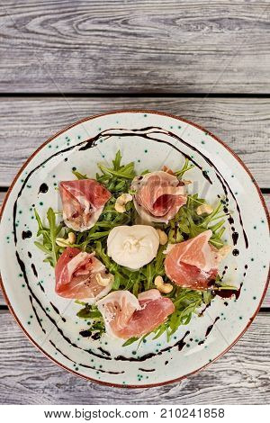 Delicatessen salad with burrata cheese, top view. Delicious salad with arugula, prosciutto and burrata cheese. Appetizing dinner on plate.