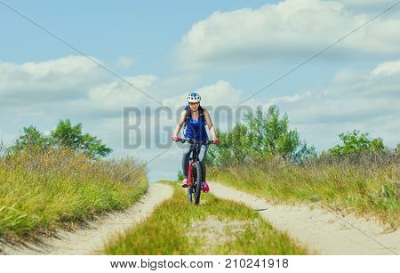One young woman - an athlete in a helmet riding a mountain bike outside the city on the road on a summer day.