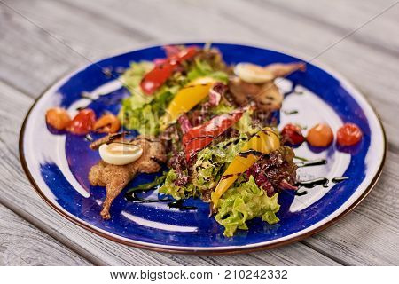 Lettuce salad with quail meat and nut sauce. Quail with green salad on blue porcelain plate. Delicious food on restaurant table.