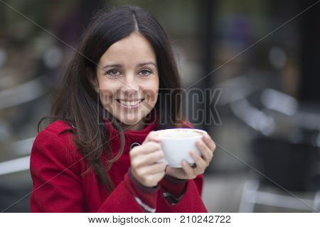 a young woman enjoying a cup of coffee