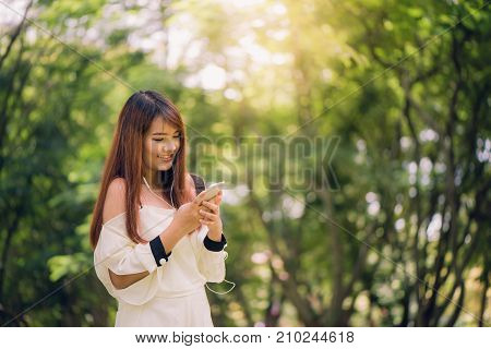 Cute asian woman is reading pleasant text message on mobile phone while sitting in park in warm spring daygorgeous female listening to music in headphones and searching information on cell telephone.