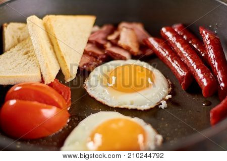 Full english breakfast in pan. English breakfast in pan with fried eggs, sausages, bacon, tomatoes and toasts. Traditional english breakfast.