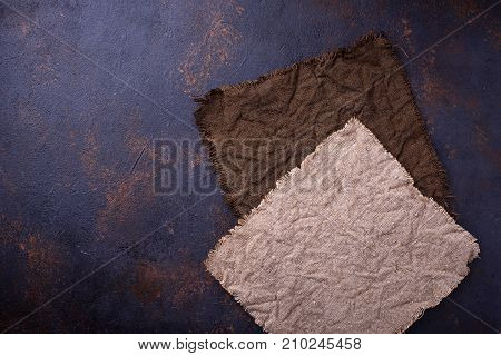 Two brown linen tablecloth on concrete background. Top view