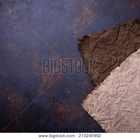 Two brown linen tablecloth on concrete background. Top view, square image