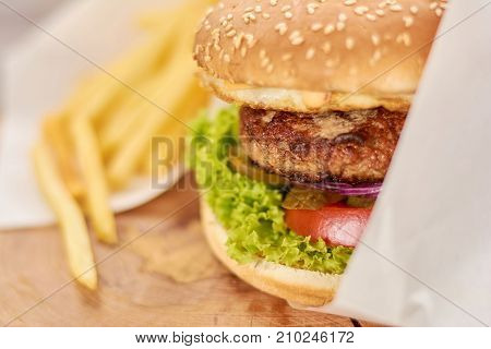 Appetizing fresh burger close up. Delicious burger with meat, lettuce, tomatoes, cheese, pickled cucumber close up. Classsic american food.