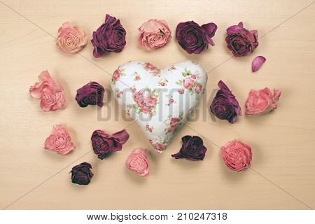 Hearts and wilted roses on pastel wooden background.Valentines day greeting card.Top view with copy space
