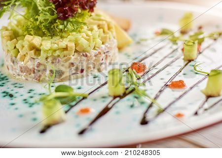 Salad with herring, avocado and toasts. Delicatessen salad with herring in belgian style, avocado and toasts. Delicious food on plate.