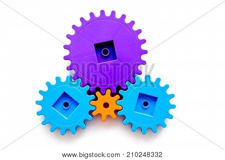moving forward concept, ideal operating principle with gears and wheels on white desk background top view