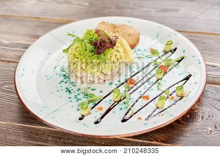 Delicious salad on wooden table. Appetizing salad with herring, avocado and toasts in restaurant. Tasty dinner on plate.
