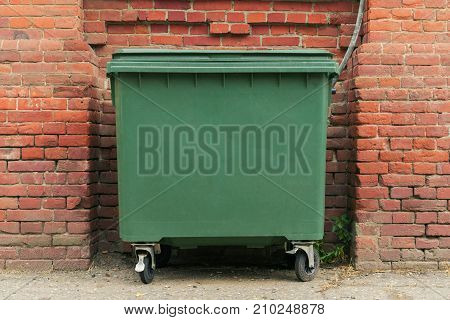 city green garbage container rubbish bin dustbins outside against brick wall background with copy space