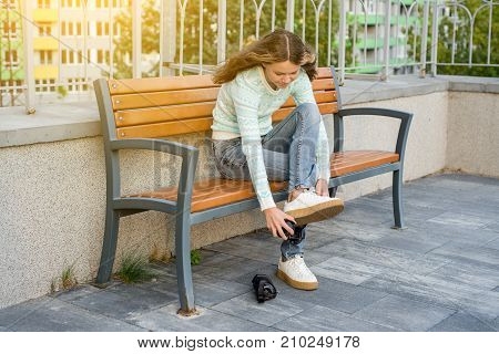 A teenage girl sitting on a bench in the city dresses wheels on sneakers