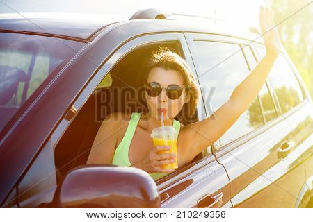 A happy woman driver stops to relax enjoy the journey drink orange juice and wave your hand