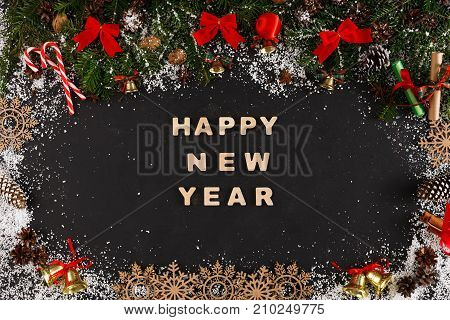 Happy new year greeting, decoration background, top view on pine tree twigs with pine cones, nuts, red bows, bells and snowflakes frame with wooden letters