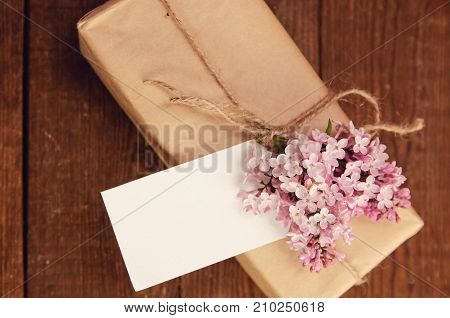 Gift wrapped with kraft paper on a wooden table tied with a rope with a bouquet of pink lilac attached greeting cards