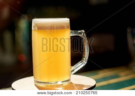 Glass of light beer on bar table. Mug of fresh drink on dark pub background. Still life of glass with lager beer.