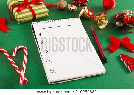 Christmas wish list or letter to Santa. Notepad with copy space on green messy table background. Preparing for winter holidays