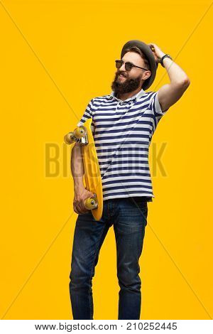 Young hipster man posing with yellow board looking confidently away on orange background.