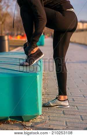 Closeup look from a sporty woman tying her shoelaces