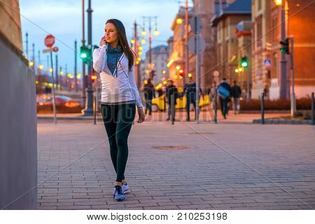 A beautiful young woman wearing sportswear and standing on the street in the city lights at night falls
