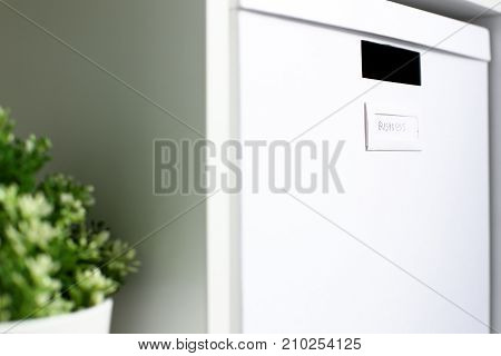White cardboard box with business sign stand on cupboard shelf as symbol of order and workspace optimization closeup