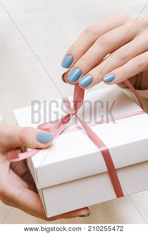 Female hands with blue manicure holding white gift box.