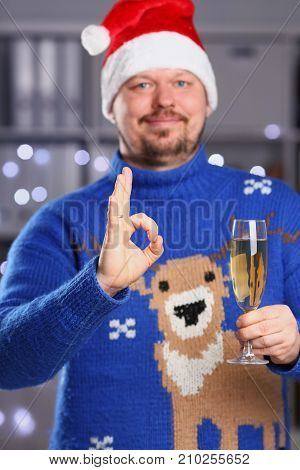 Man wearing warm blue deer sweater hold in arm champagne goblet show okay or confirm during festive speech with glowing garland in background closeup. Mediation solution expression adviser participate