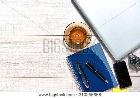 View of a wooden table with a laptop, mobile, notebook, glasses, watch, pen and a cup of coffee on the side of it