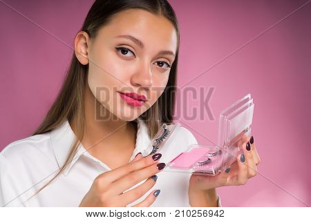 young beautiful girl holding a package with black overhead ladders