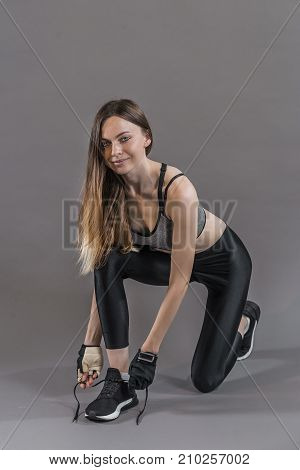 Fair hair girl is doing up her left foot black and white trainer, preparing for the workout in the grey background, isolated