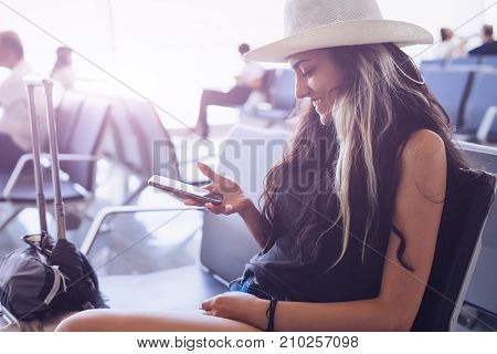 Woman on smartphone,waiting boarding time in terminal,use travel app,smiling.Travel vacations concept