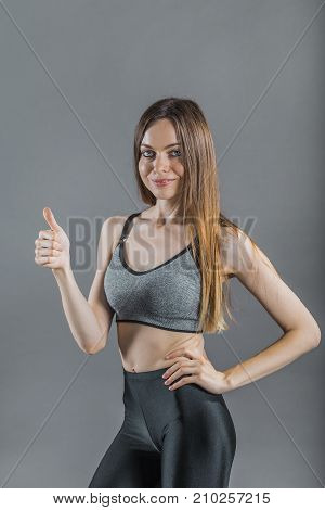 Pretty dark hair sportswoman wearing a grey top show thumb up sign in the isolated background