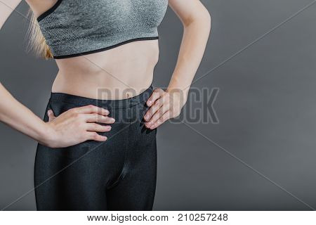 Pretty dark hair sportswoman wearing a grey top in the grey isolated background