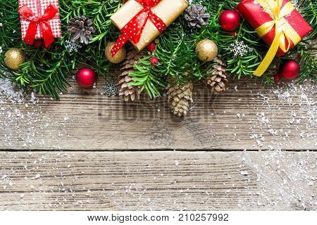 Christmas background with fir tree branches decorations pine cones and gift boxes on rustic wooden board. mock up. top view with copy space