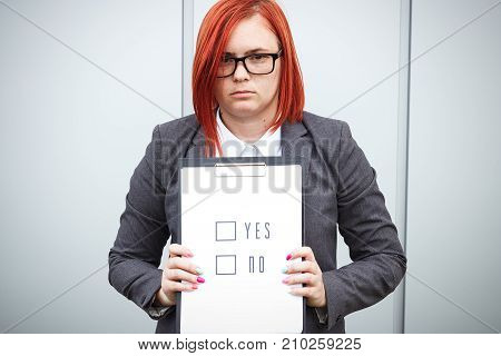 Business Concept Of Choice And Voting. A Woman In A Suit And Glasses Makes A Yes Or No Choice. With