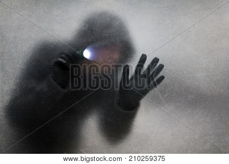 Thief with flashlight behind a dusty scratched glass