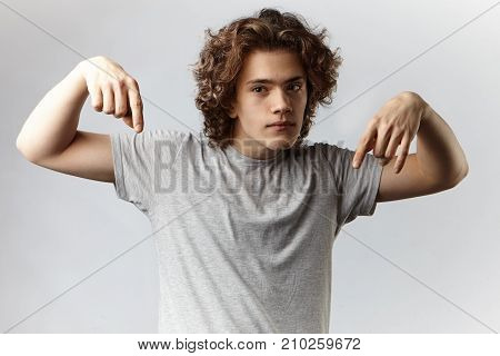 Check this out. Cropped shot of clean shaven male student posing at blank studio wall pointing index fingers down at his grey t-shirt with copy space for your information or advertising content