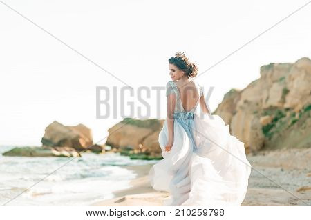 Fashion bride in luxury wedding dress with bouquet at the sea side. Wedding by the sea. Bride walking around the sea near the place of the wedding ceremony.
