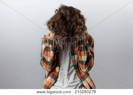 Studio shot of depressed unrecognizable teenager bending down head with his wavy hair covering face feeling unhappy and stressed out because of problems at school. Youth loneliness and depression