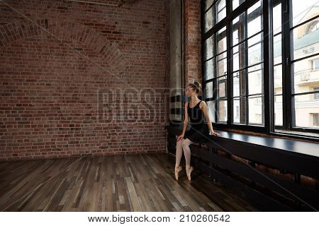 Full lenght indoor picture of beautiful graceful professional ballerina with hair bun waiting for her students sitting on windowsill in spacious studio with blank brick wall with copyspace for your ad