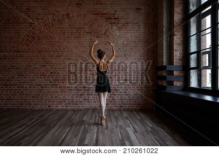 People art theatre choreoography and dance concept. Back view of slender beautiful young ballerina in black dress standing en pointes in the middle of ballet studio practicing center work