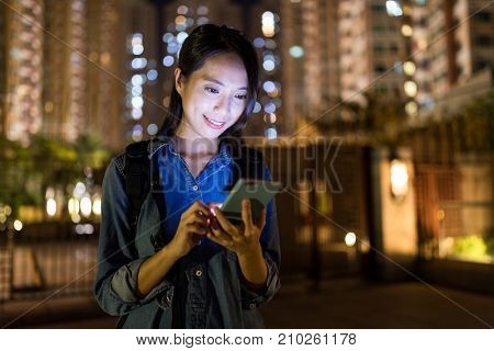 Woman using smart phone in the city at night