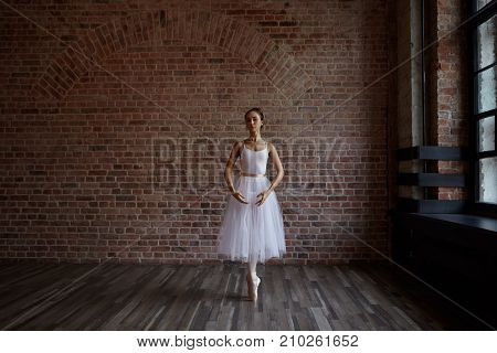Attractive hardworking young ballerina wearing white pack and pointe shoes practicing center worrk standing on toes against red brick wall background with copy space for your advertising content