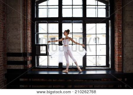 Portrait of beautiful professional young female ballet dancer with graceful slim body training indoors standing in pose at large window dressed in white ballet skirt having concentrated look