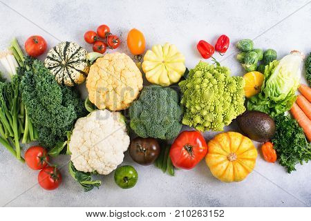 Overhead table top view colorful rainbow vegetables on the light grey background, copy space for text below, selective focus