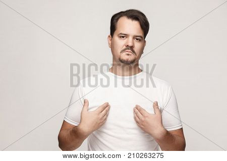 Arrogant And Proud Adult Man Pointing Hands Himself And Looking At Camera.