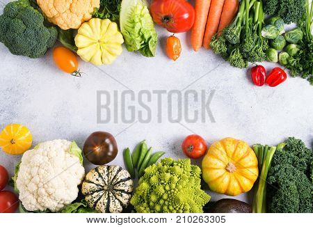 Healthy eating, top view of colorful rainbow vegetables on the light grey background, copy space for text in the middle, selective focus