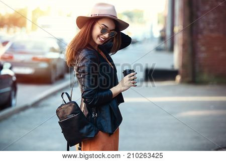 Close-up Fashion woman portrait of young pretty trendy girl posing at the city, autumn street fashion, holding retro fedora hat popular until the 60s. laughing and smiling portrait.trendy